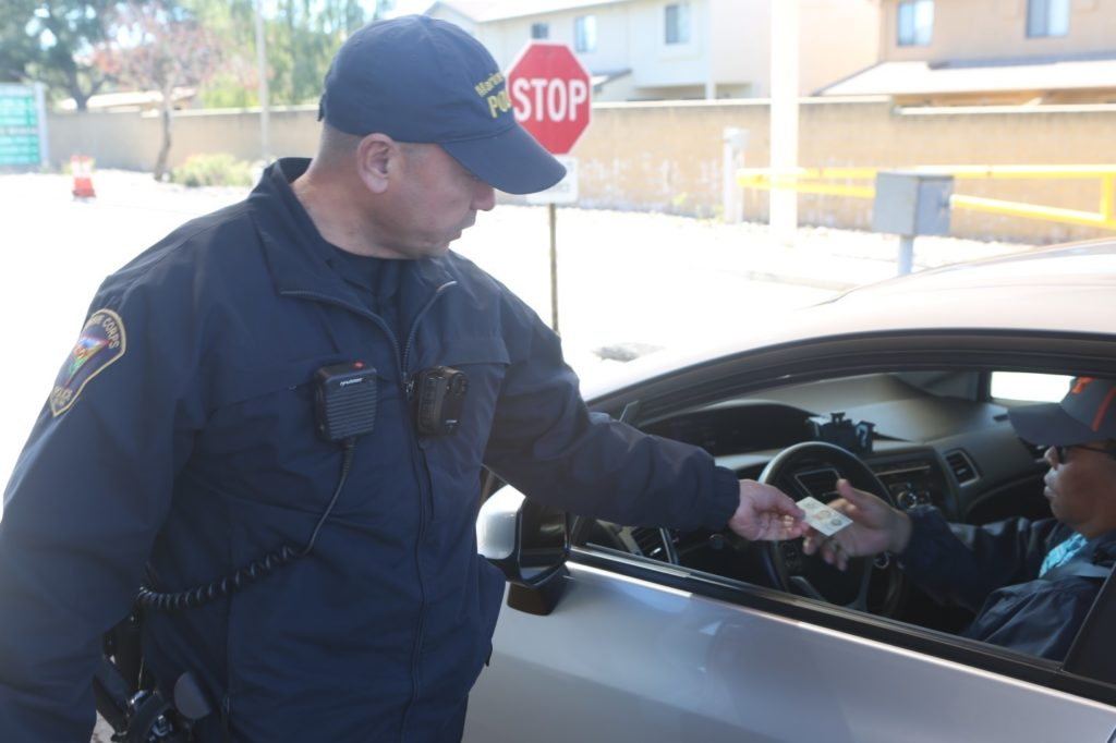 officer gettting identification at a traffic stop. article is about police body cams