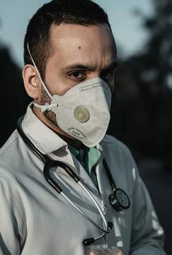 wearing face mask to protect against coronavirus. He also has a steathascope around neck. this illustration is related to the need for Healthcare Cybersecurity.