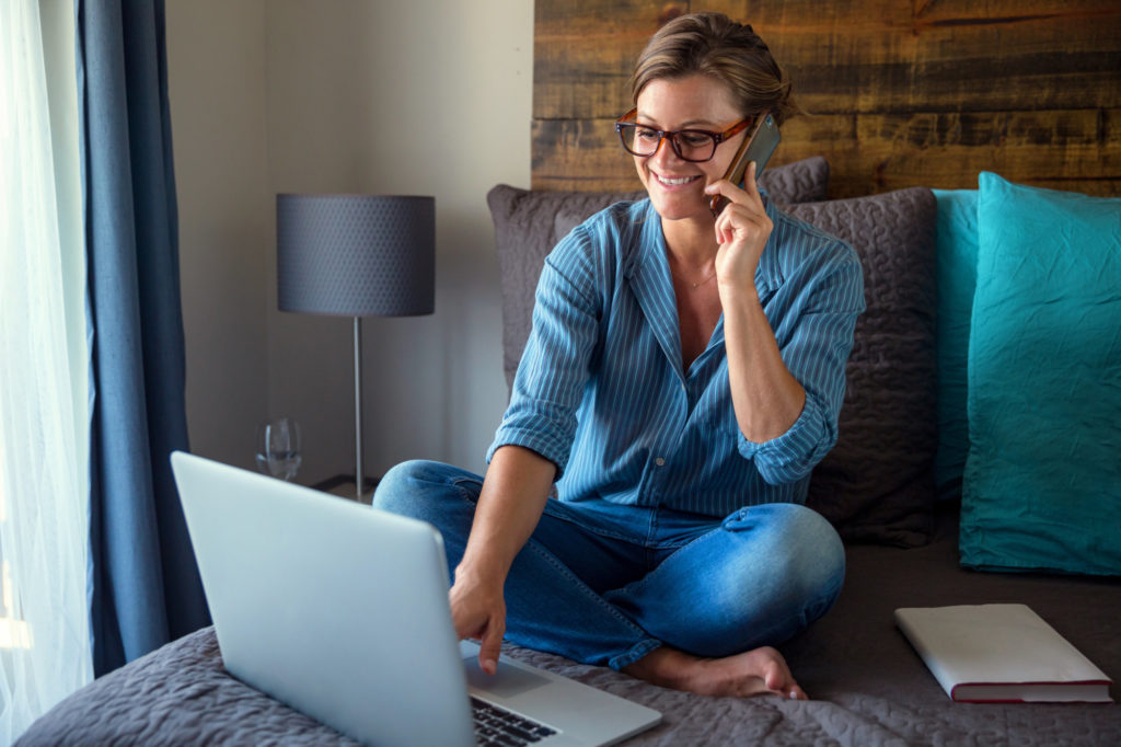 remote worker sitting on bed talking on cell phone with laptop in front of her. She is a remote worker for a small business, doing remote IT contract work.
