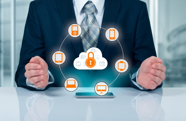 man in a suit with security lock inside a cloud and technology devices surrounding it in a circle