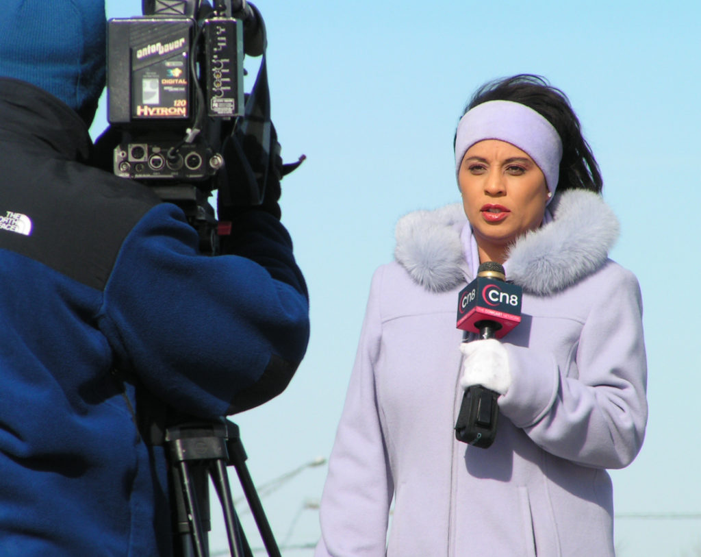 woman in purple coat doing live mobile broadcast