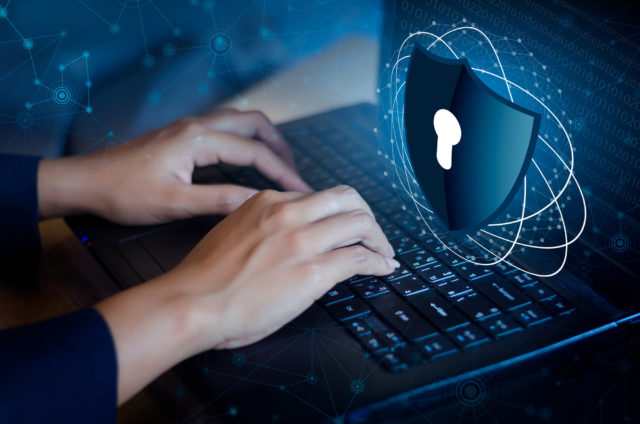 Cybersecurity protection. Protect your data from being compromised, picture is of hands on laptop and the screen is a lock.